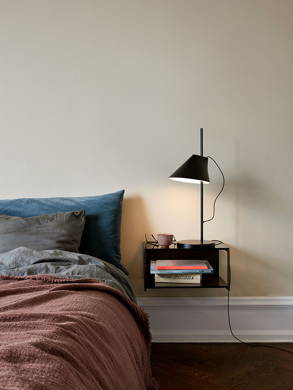 The black Yuh table lamp in a bedroom, on a nightstand.