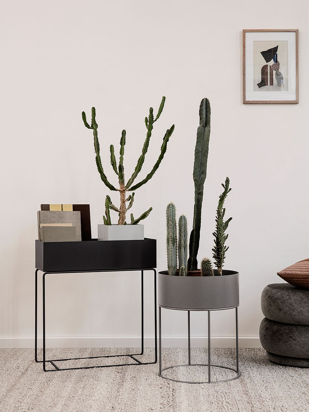 Ferm Living's round Plant Box in warm grey and rectangular Plant Box in black.