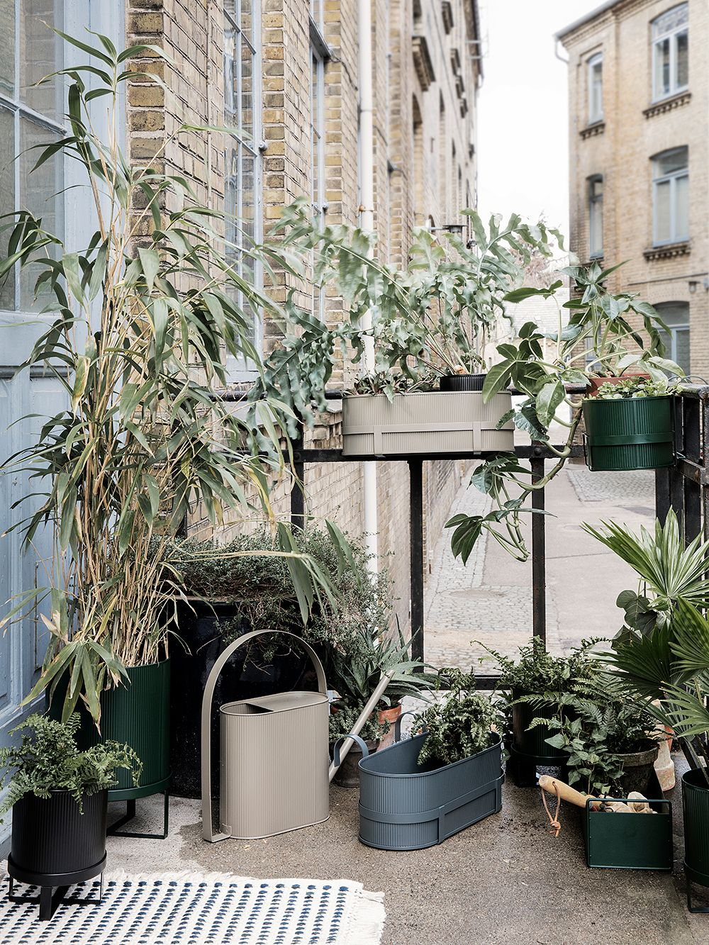 Ferm Living's Bau balcony boxes and pots on a balcony with a city view.