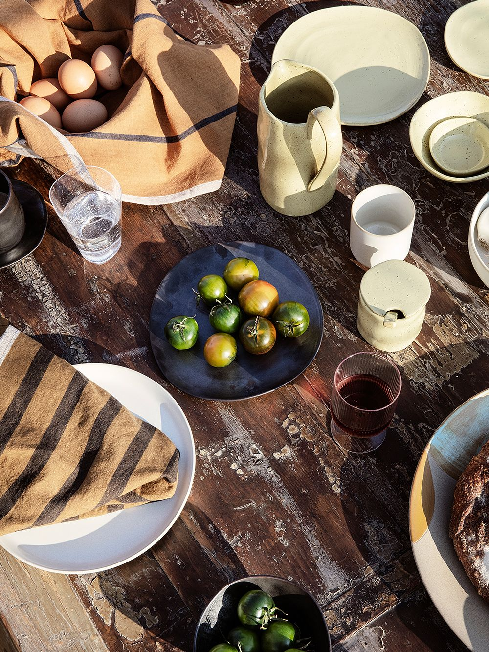 Ferm Living's Flow tableware in a table setting outdoors.