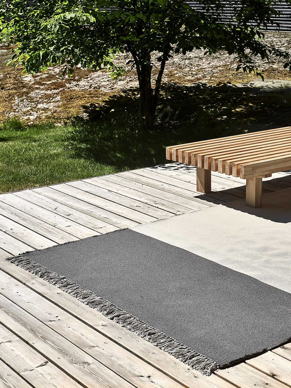 The Pond rug by Woodnotes on a terrace.