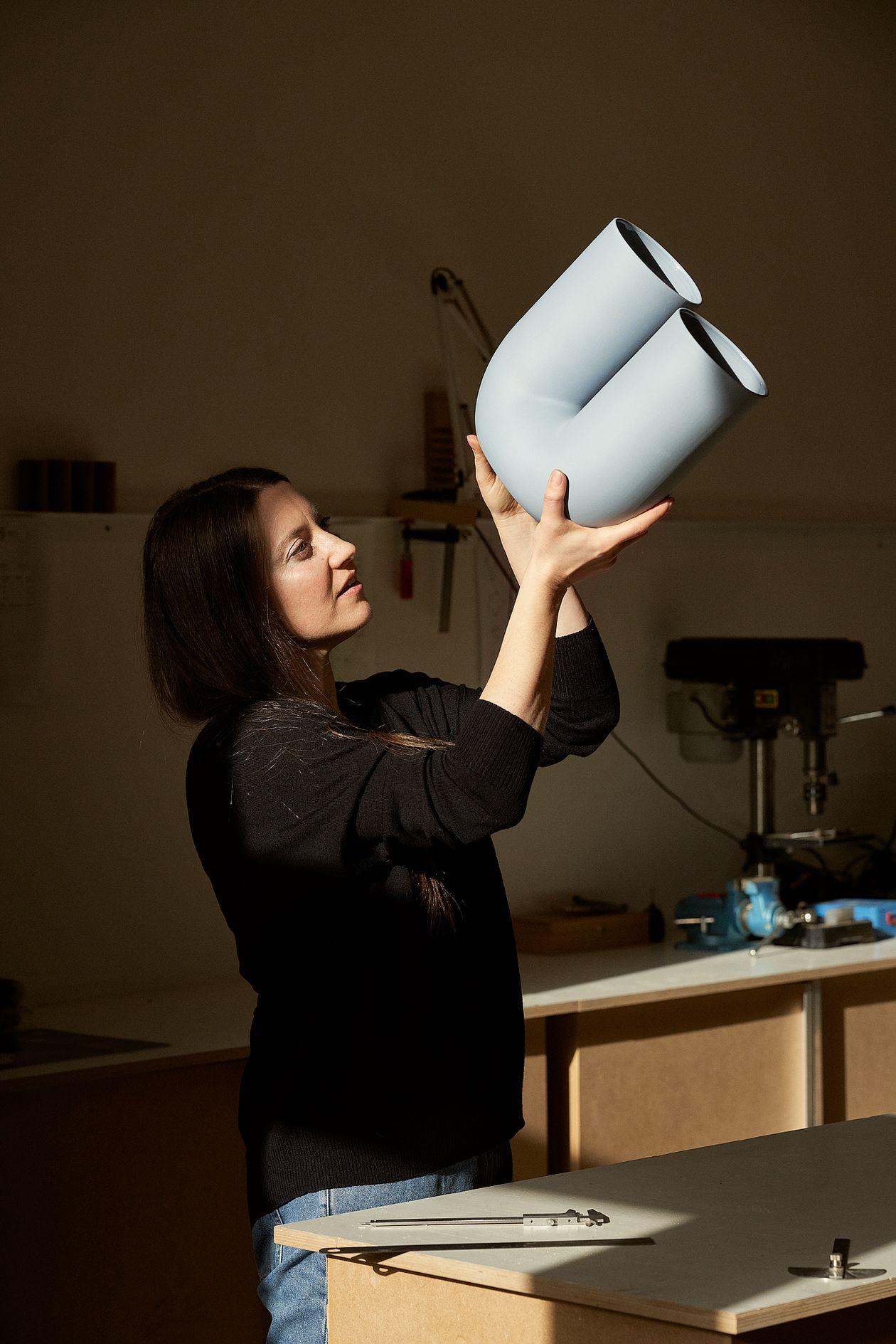 Rachel Griffin looking at her design, the Kink vase.