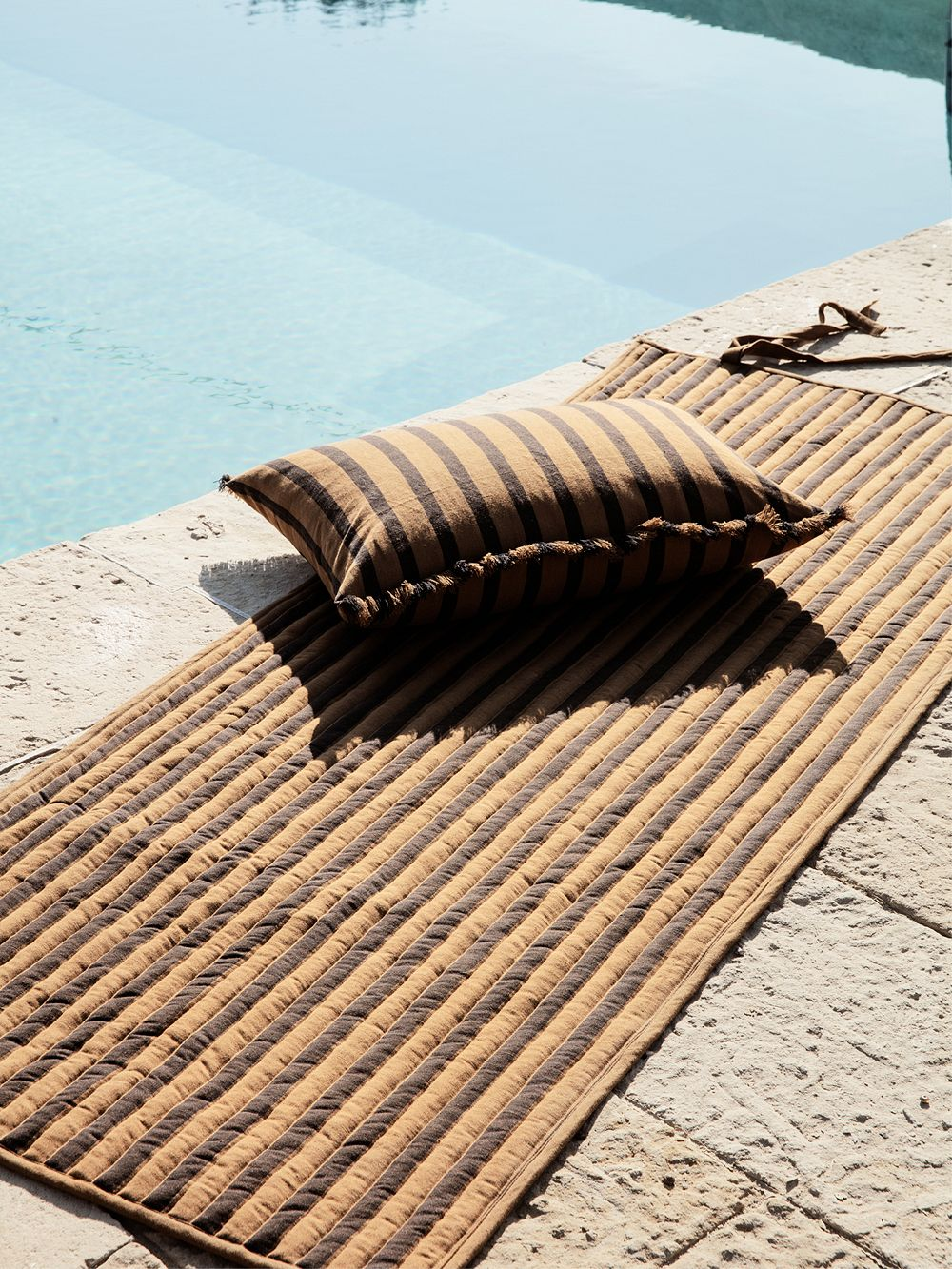 Ferm Living's Way cushion beside a swimming pool.