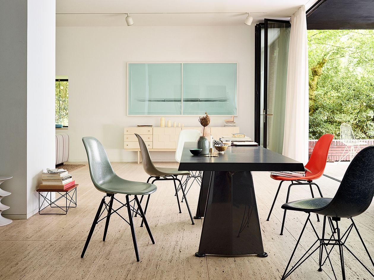 Vitra's Trapezè dining table designed by Jean Prouvé, accompanied by Vitra's Eames chairs.