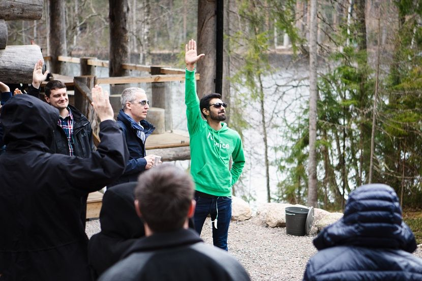 A Futurice employee in a green hoodie, raising his hand amongst other camp participants.