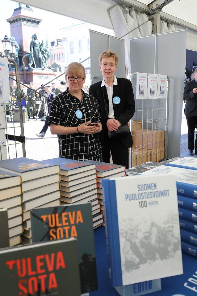Editan myyntipisteessä päivystivät projektikoordinaattori Crisme Kotilainen sekä Suomen puolustusvoimat 100 vuotta -kirjan kustannustoimittaja Arja Olin. Kustannustoimittajan rooli kirjojen usein laajan tekijäjoukon paimentajana päätoimittajan vastinparina on elintärkeä kirjan valmistumisen kannalta. Juhlateoksen toimitustyötä Arja Olin piti erittäin mielenkiintoisena ja palkitsevana. Sotilastaustaisten kirjoittajien kanssa työskentelyssä on etunsa mm. aikataulujen osalta.