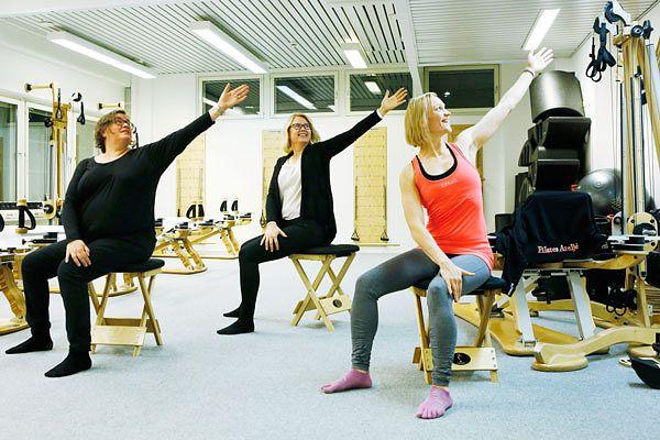 Toimitusjohtaja Anu Raita Pilates Ateljésta (oik.) opastaa HyvinVointiTalon muita yrittäjäkollegoita Virpi Kunnas-Helmistä (vas.) ja Tiina Kaivolaa kyljen venyttämisessä.