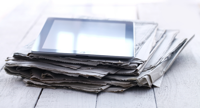 A tablet on top of a pile of newspapers.