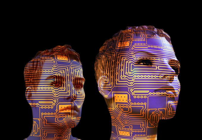 Two human-like heads with computer machinery images projected on to the faces.