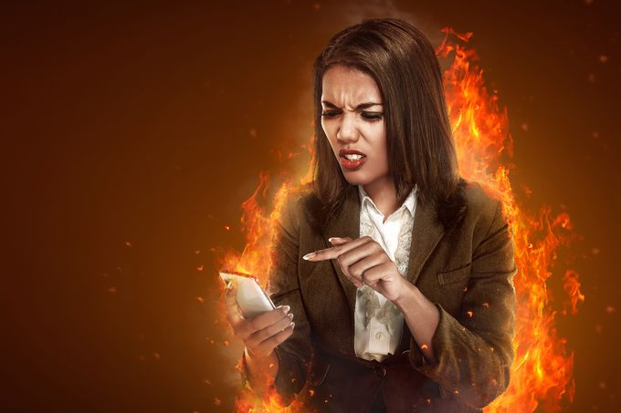 An angry business woman pointing a mobile phone screen scrinching, illustrated flames behind her.