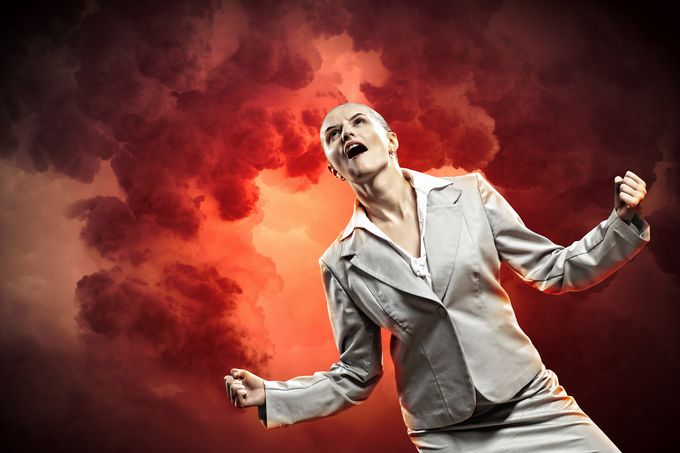 An angry business woman screaming under a smoky, red sky.