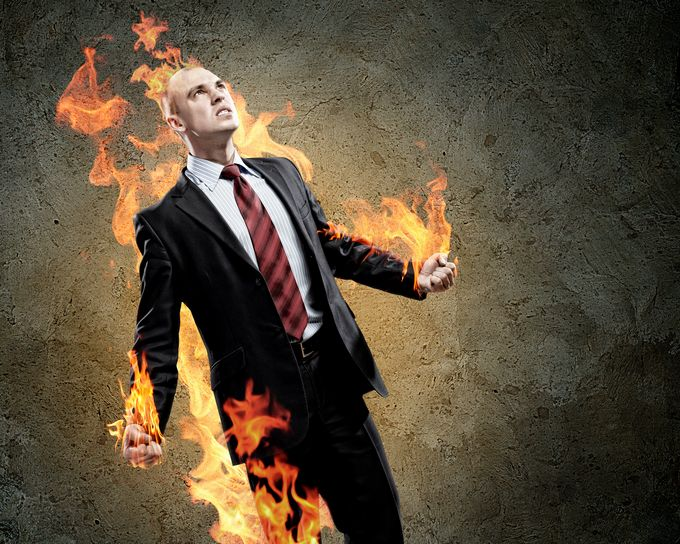 An angry business man, illustrated flames rising behind him
