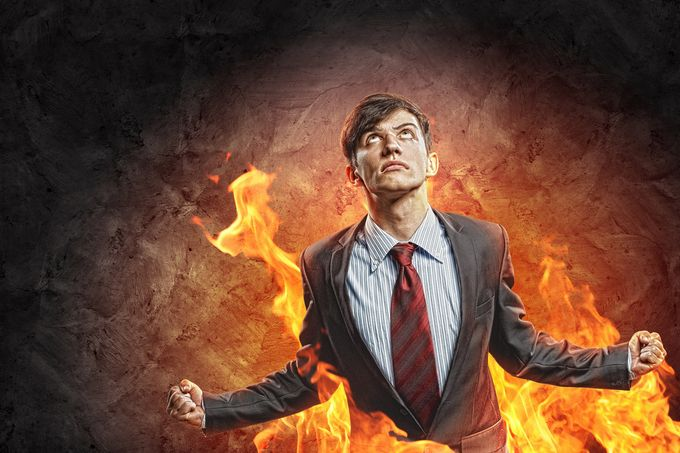 An angry business man trying to contain his rage in front of a flaming background.