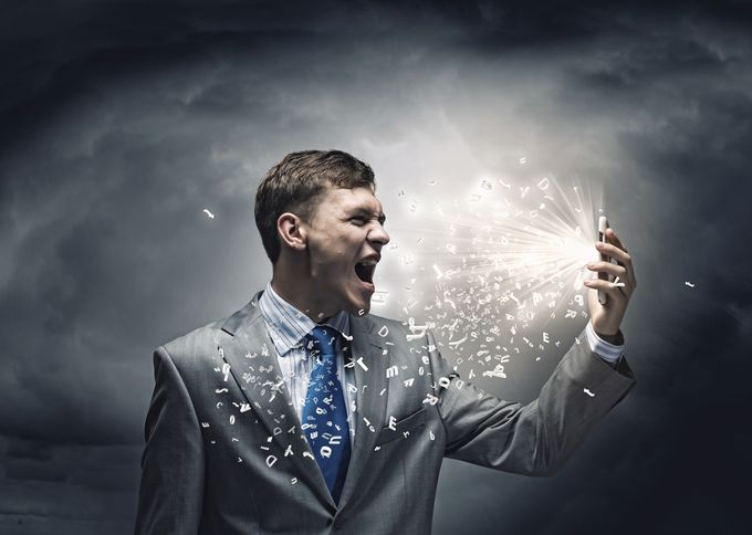An angry business man screaming to a mobile phone in front of a stormy, dark background.