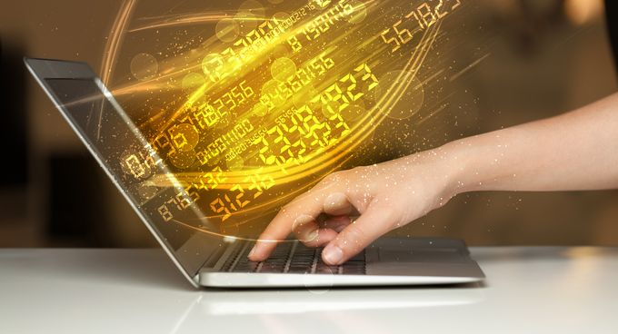 A hand pushing a key on a laptop, glowing yellow numbers exploding out of the screen.