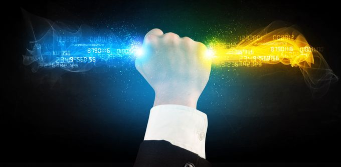 A fist of a business person rising up in the air, holding a wand of blue and yellow digital data stream.