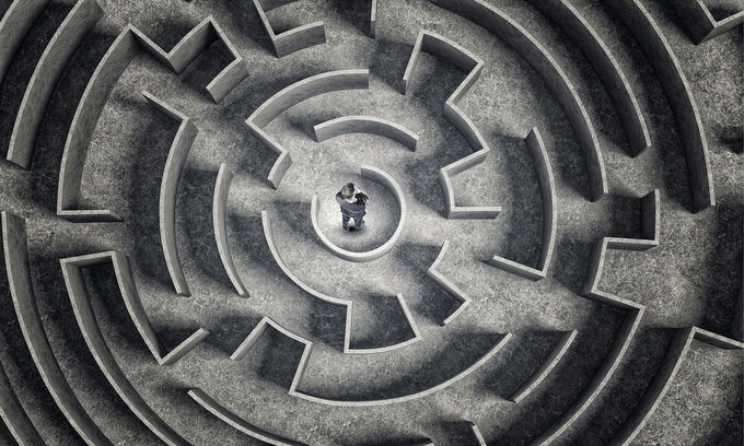 A business man in the middle of a round labyrinth.