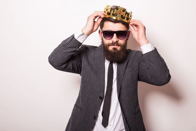 A man in a suit wearing sunglasses and fitting a crown on his head.