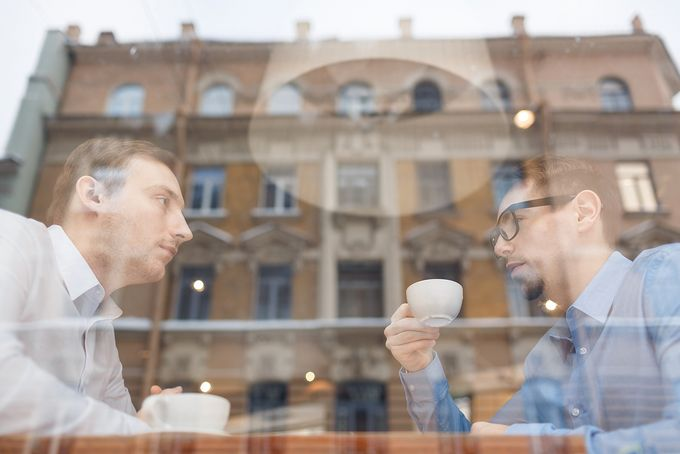 A salesman listening to a client behind the window of a coffee house.