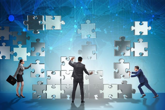 Business people gathering illustrated pieces of a puzzle together