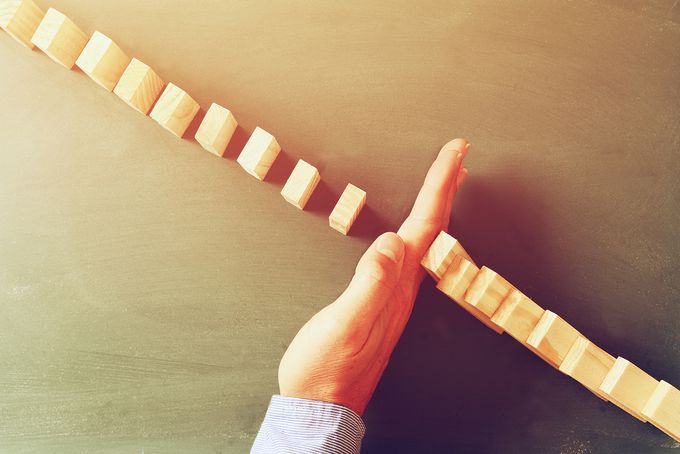 A hand stopping a chain of wooden domino blocks from falling.