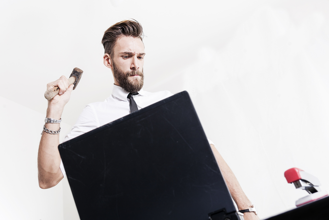 A sharp-dressed designer staring at an open laptop serious, holding up a hammer.