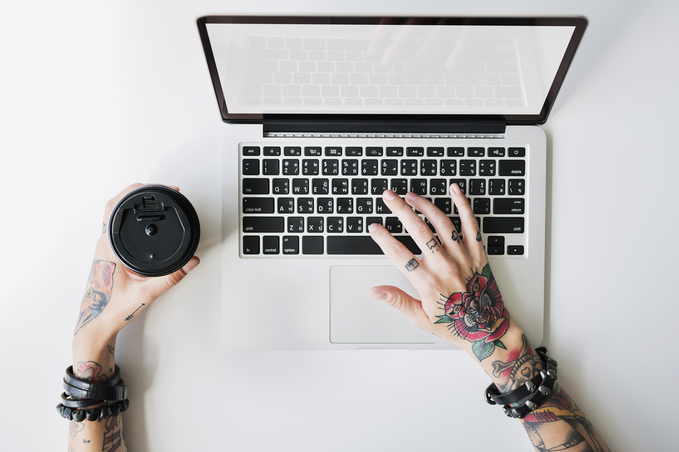 Tattooed hand on a laptop keyboard, other hand holding a takeaway coffee.