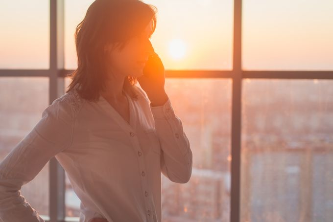 A woman talking on the phone in front of a large window, setting sun shining through.