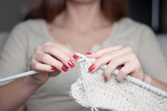 Womans hands knitting, nails polished red.