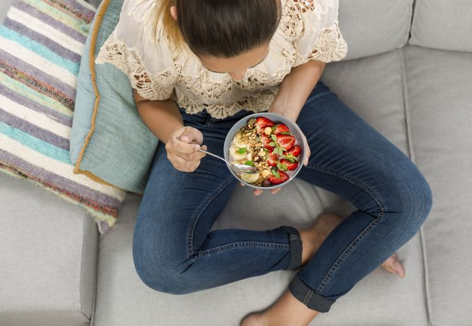 A woman pictured from above, eating a bowl of granola and fruits on a sofa.