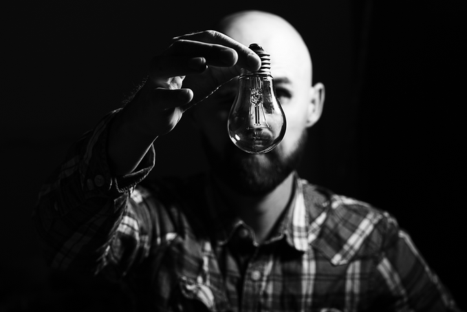 Man in a black and white picture holding a lightbulb in front of his face.