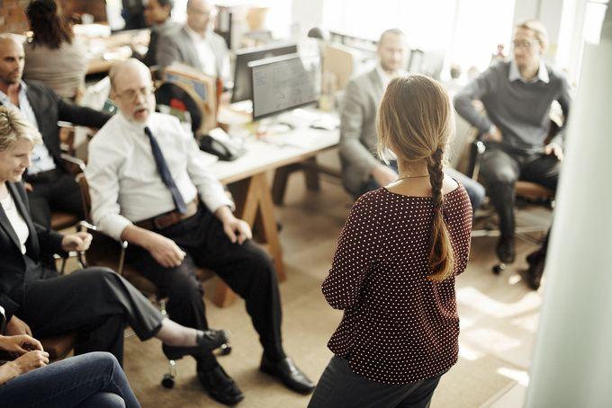 A woman standing in front of sitting people in a modern office, talking to the audience.