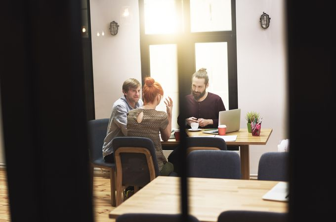 Three people talking behind the closed doors around the table in a conference room.