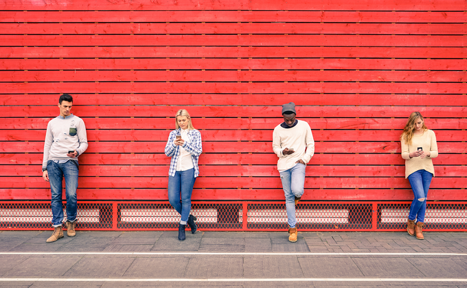 Four young people leaning into a red wall, browsing their mobile phones.