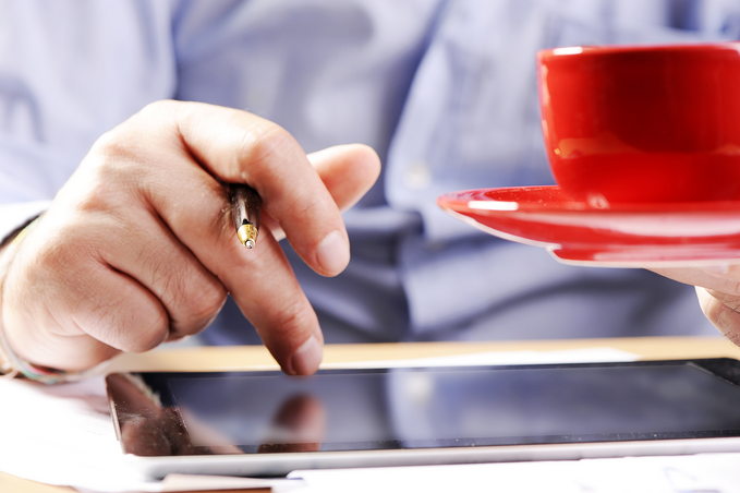 Person holding a red coffee cup while using their other hand to operate a tablet.