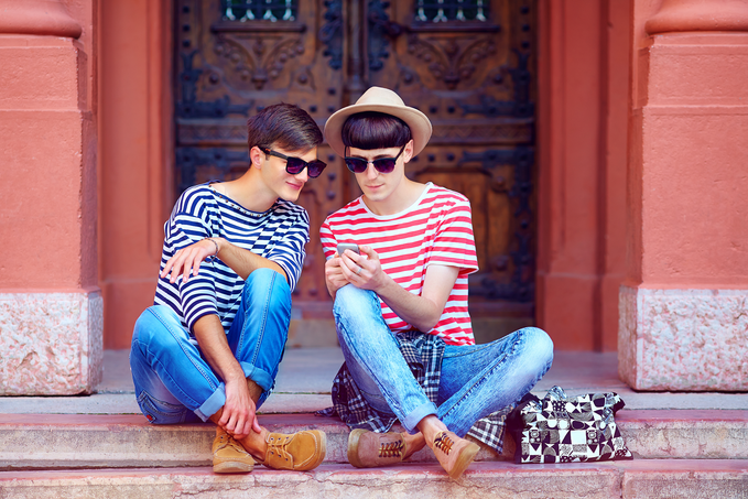 Two young persons in triped t-shirts looking at the screen of a mobile phone the other one is showing, sitting on the stairs of a red building.