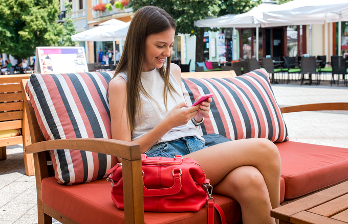 A young woman sitting on a coffee house terrace, smiling and checking her mobile phone.