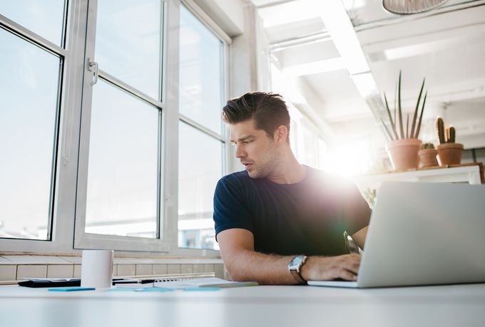 A journalist writing on a laptop in a white, sunny office.