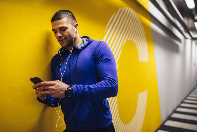 A trainer on a gym leaning against a yellow wall, looking at his mobile phone.