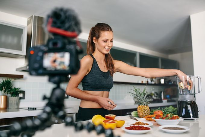 An athletic woman mixing ingredients on a blender in front of a video camera.