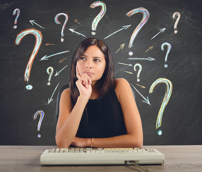 A woman sitting in front of a computer keyboard wondering, question marks drawn around her head.