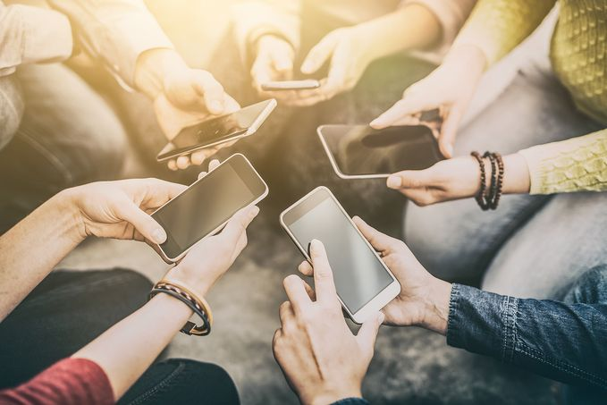 Hands of five people holding mobile phones.