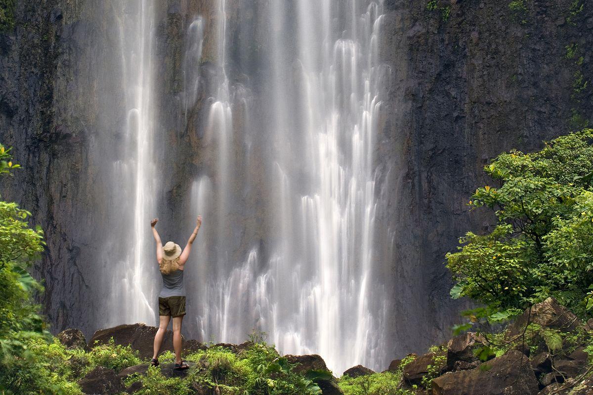 Jeune femme au pied d'une cascade en Guadeloupe