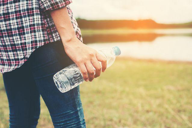 Une personne qui tient une bouteille d'eau.