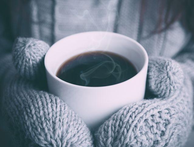 Une personne qui tient une tasse de café