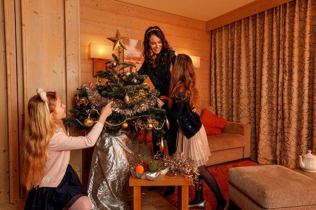 Une famille qui décore un sapin de Noël