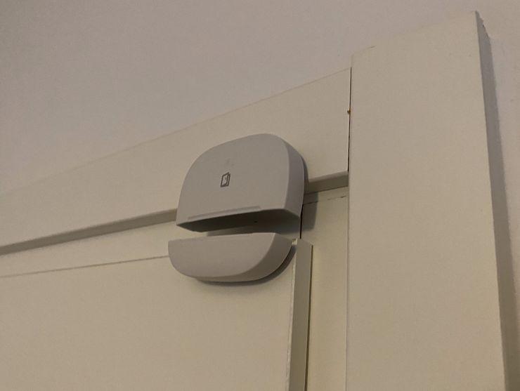 SmartThings-monitoimitunnistin asennettu oveen ja sen karmiin.