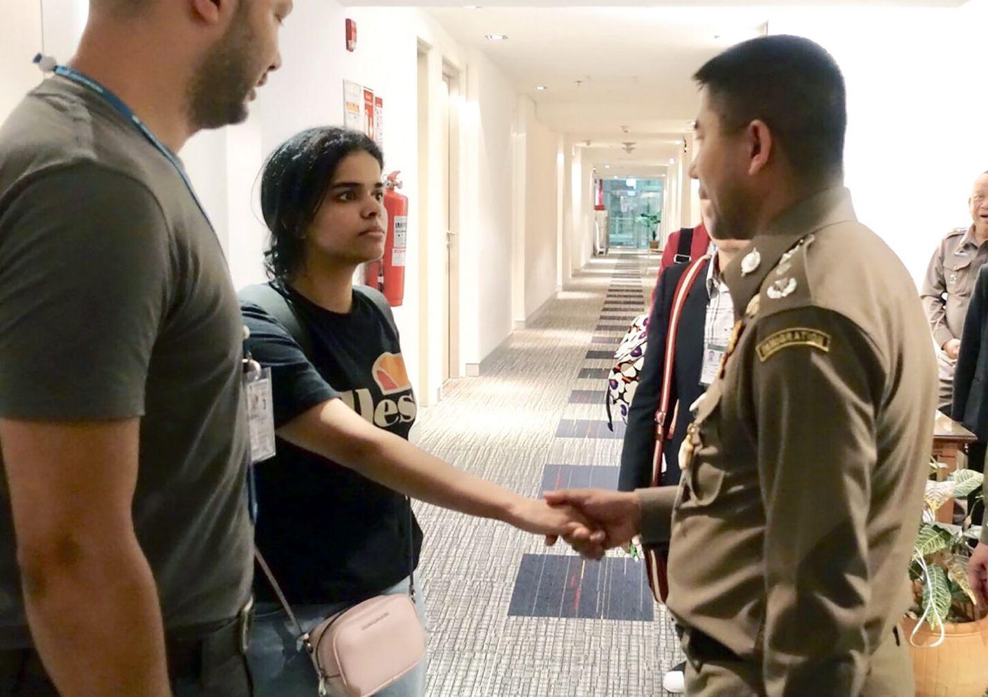 Rahaf Mohammed al-Qunun (vas.) tervehti Thaimaan maahanmuuttopoliisin päällikköä Surachet Hakparnia maanantaina Bangkokin lentoasemalla.