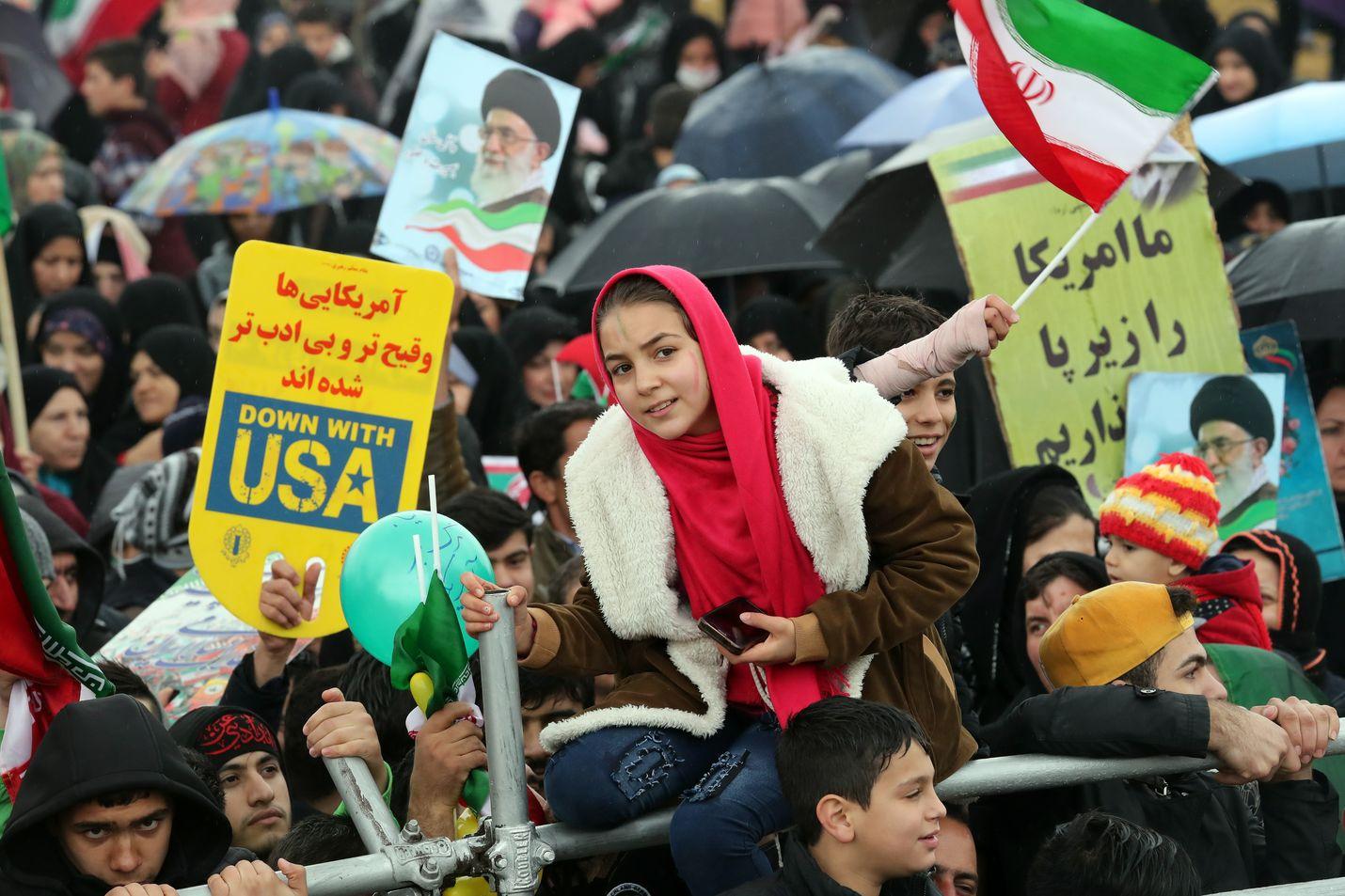 Iranin vallankumousta juhlivat kantoivat muun muassa Yhdysvaltain vastaisia kylttejä Teheranissa maanantaina.