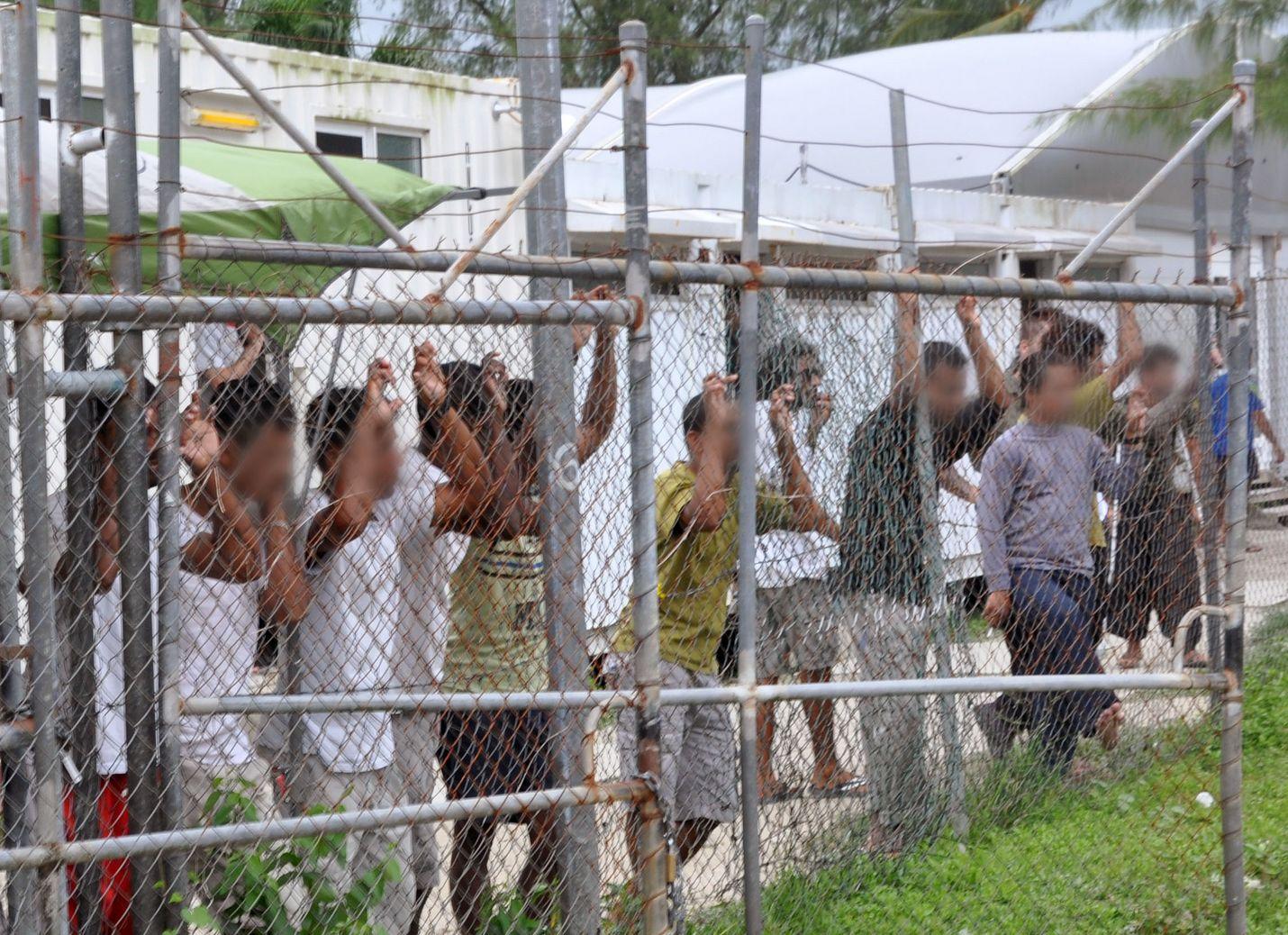 Turvapaikanhakijat katselivat tiedotusvälineiden edustajia Australian vastaanottokeskuksen aidan takaa Manusin saarella Papua-Uudessa-Guineassa vuonna 2014.